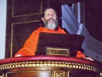 Swamiji at lectern 200x150px -80kb